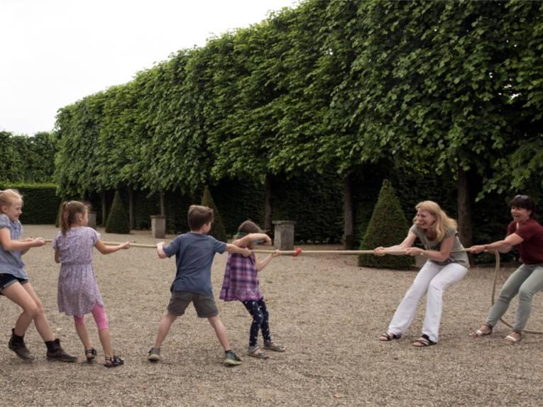 Kinder und Erwachsene spielen Tauziehen.