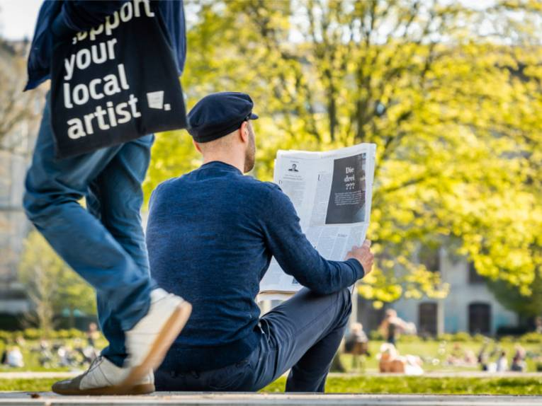 Ein Mann liest im Park eine Zeitung.
