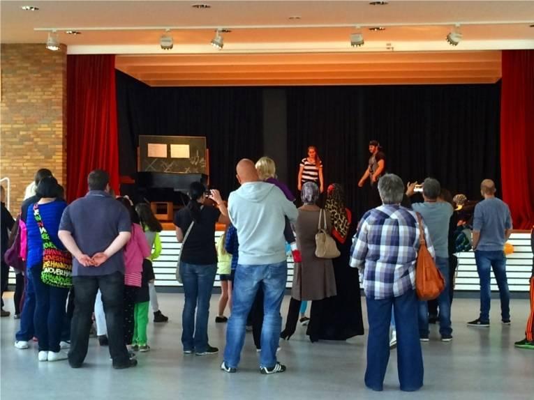 Die Besucherinnen und Besucher schauen sich die Hip Hop AG der Heisterbergschule an. Die Aufführung wurde in einem größeren Saal auf einer Bühne aufgeführt.