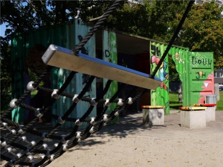 Auf dem Bild ist der Jugendplatz an der Fösse zu sehen, auf der ein bemalter Spielcontainer, ein Klettergerüst und Sitzmöglichkeiten stehen.