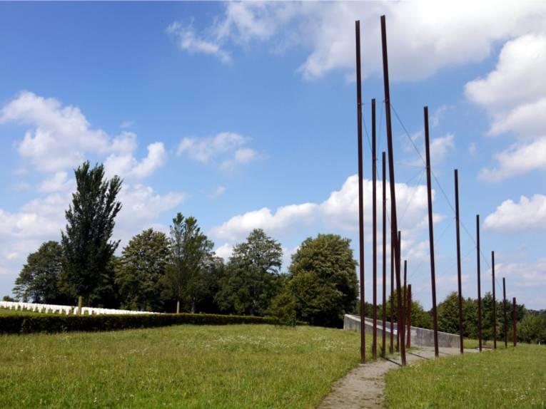 Ein Mahnmal aus mehreren verschieden große Pfählen, die von klein nach groß angeordnet sind, die sich in der Mitte treffen und wieder von groß nach klein verlaufen. Dieses Mahnmal steht in einer grünen Landschaft in Ahlem.