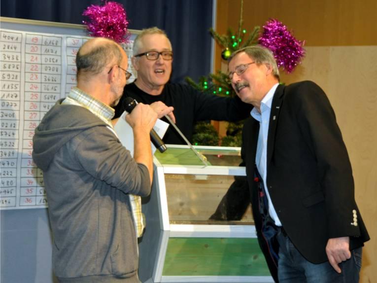 Bezirksbürgermeister Harry Grunenberg (re.) zieht mit geschlossenen Augen das Gewinnerlos für den Hauptpreis der diesjährigen Stiftungs-Lotterie.