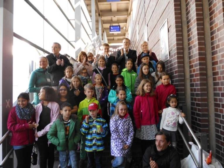 Eine Gruppe von Kindern stehen zusammen mit ein paar Erwachsenen auf einer Bahnhoftreppe.
