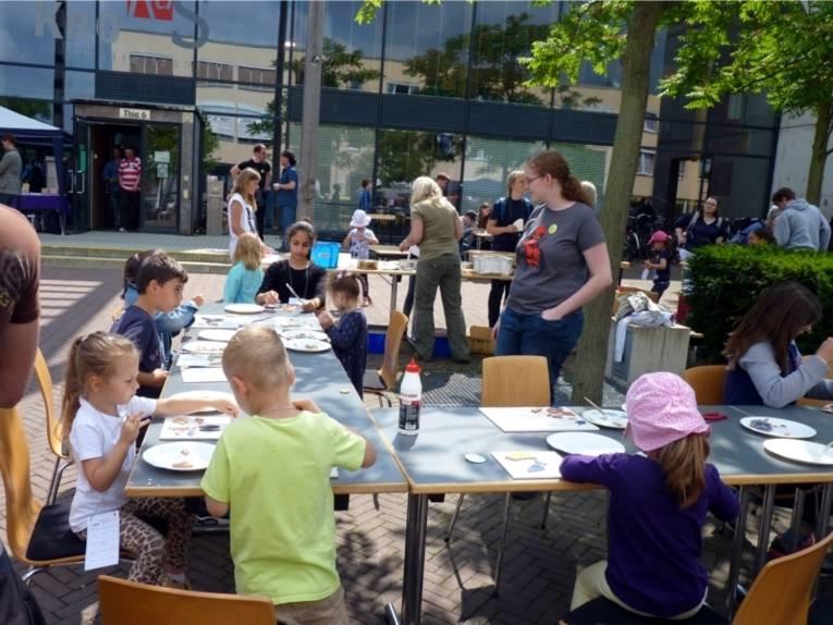 An mehreren Tischen (in U-Form gestellt) sitzen mehrere Kinder, die etwas basteln. Die Standbetreuerinnen sind dabei und helfen den Kindern.