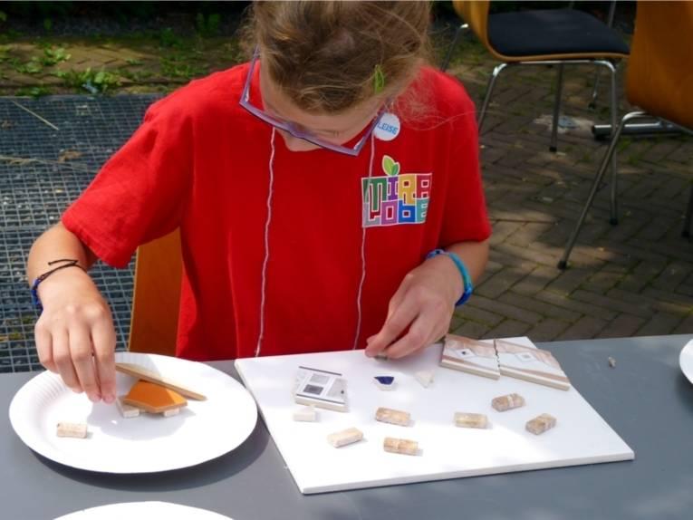Ein Mädchen fügt auf einem Einwegteller aus Pappe mehrere verschiedene Fliesenteile zusammen.