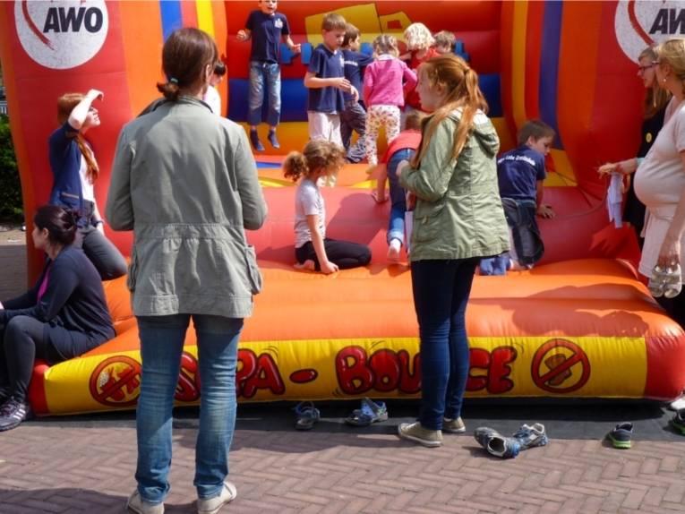 Viele Kinder spielen und tollen auf der Hüpfburg herum. Einige Elternteile warten auf ihre Kinder vor der Hüpfburg.