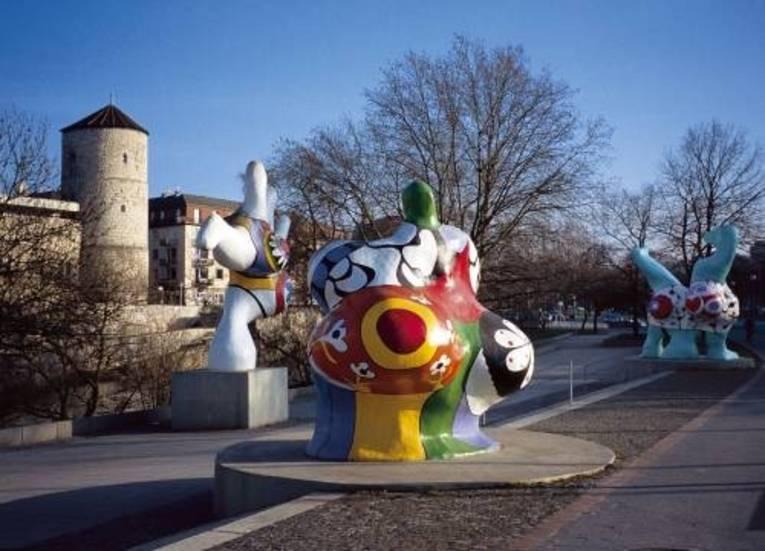Skulpturen. Im Hintergrund eine Mauer und ein Turm.