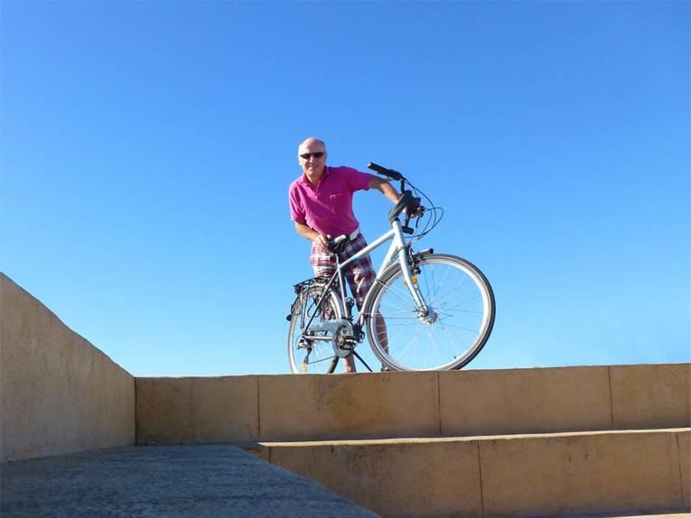 Älterer Herr steht mit Fahrrad vor blauem Himmel an einem Sommertag