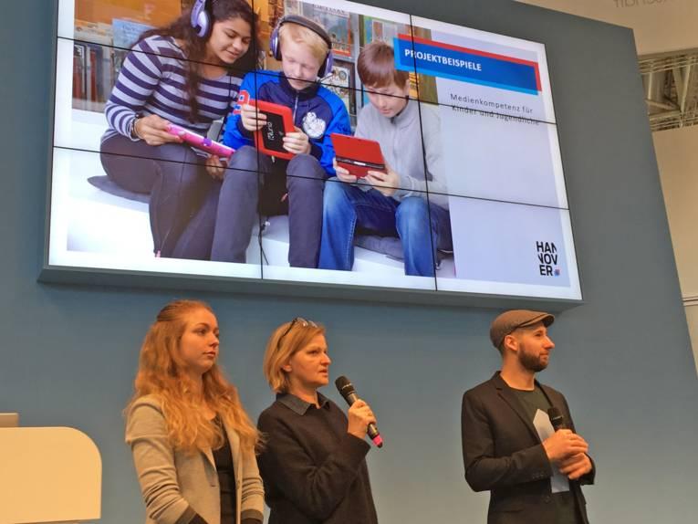 Drei Personen (eine junge Frau, eine Frau mit Mikrofon und ein Mann) stehen bei einer Vortragspräsentation auf der Bühne.