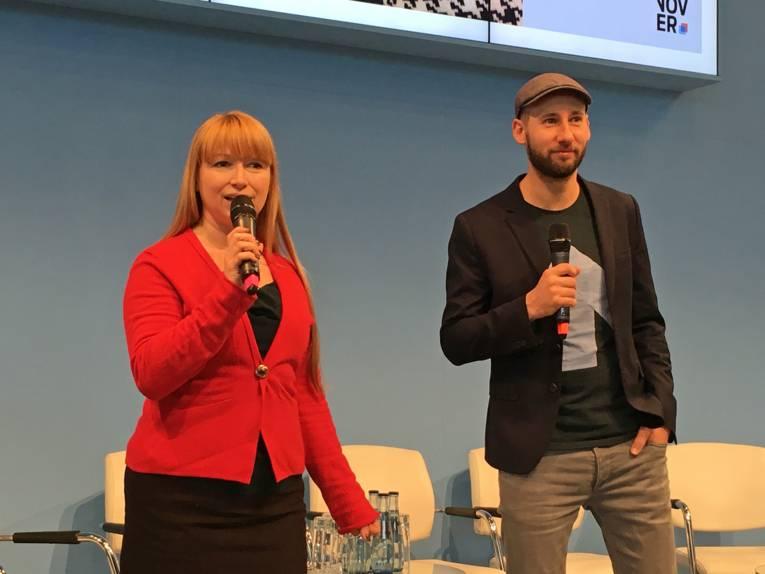 Eine Frau und ein Mann, die jeweils ein Mikrofon halten, bei einem Vortrag in einer Messehalle.