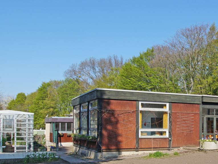 Eingang zum Verwaltungsgebäude des Schulgartens Linden; links davon steht ein Gewächshaus