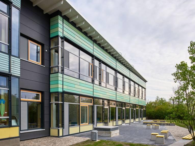 Die Außenansicht der Grundschule An der Feldbuschwende zeigt einen zweistöckigen Flachbau mit großen Fensterfronten und grüner Verkleidung, davor einen Pausenbereich mit Sitzelementen.