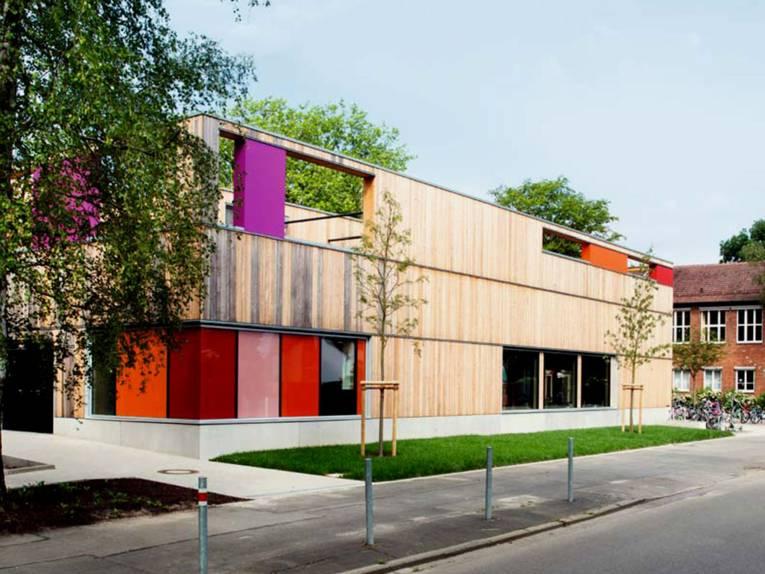 Die neugebaute Mensa der Grundschule Entenfang ist ein holzverkleideter Kubus mit barrierefreiem Zugang und bunten Tür- und Fensterelementen in orange, fliederfarben und rot.