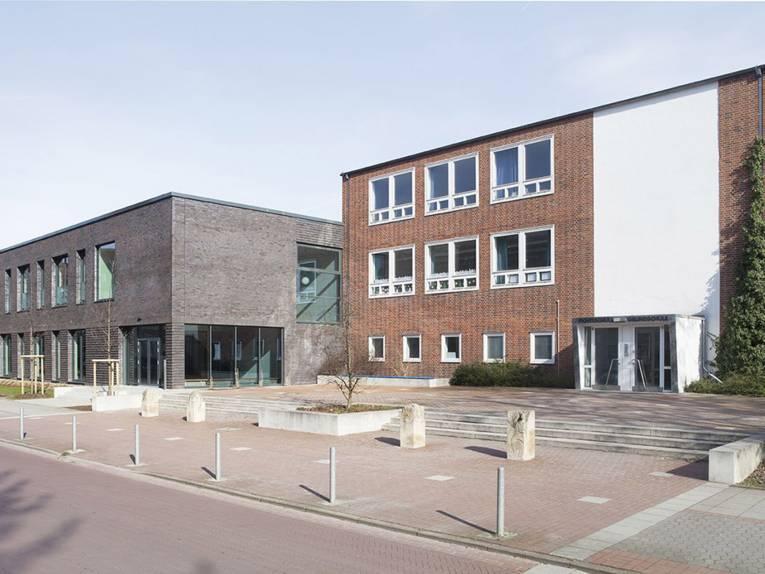 Grundschule Fichteschule: ein dreistöckiges Backsteingebäude, das von der Straße zurückgesetzt ist. Daneben der zweigeschossige Mensaanbau in dunklerem Backstein.