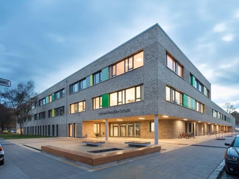 Außenaufnahme der Otfried-Preußler-Schule: ein modernes dreistöckiges Gebäude aus hellem Klinker, bei dem der Eingangsbereich etwas zurückgesetzt ist