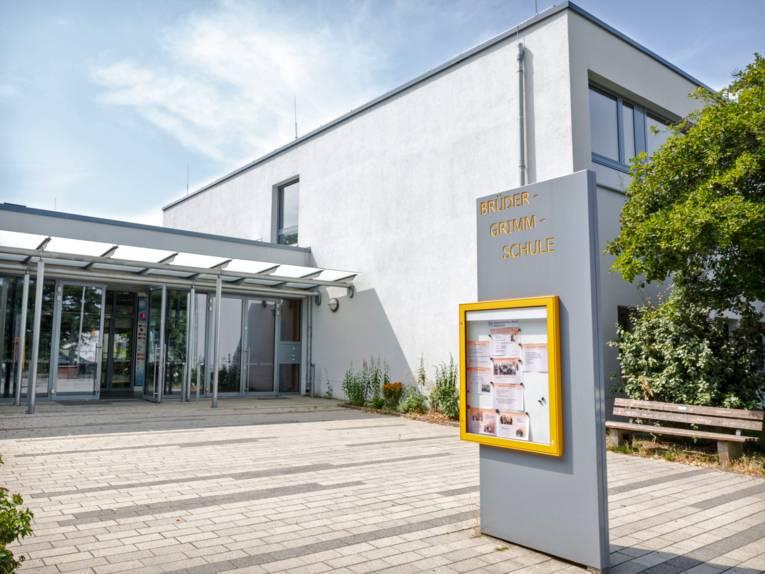 Im gepflasterten Eingangsbereich zur Brüder-Grimm-Schule steht eine Schautafel mit Aktivitäten der Schule. Die Teilansicht der Schule zeigt ein weiß verputztes, rechteckiges, zweistöckiges Gebäude mit großen Fenstern.