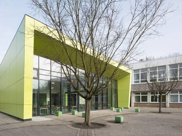 Der asymmetrisch geformte Neubau der Mensa ist an den Seiten mit hellgrünen Elementen verschalt und verfügt über eine durchgehende Fensterfront. Das Gebäude befindet sich neben dem zweigeschössigen Schulbau.