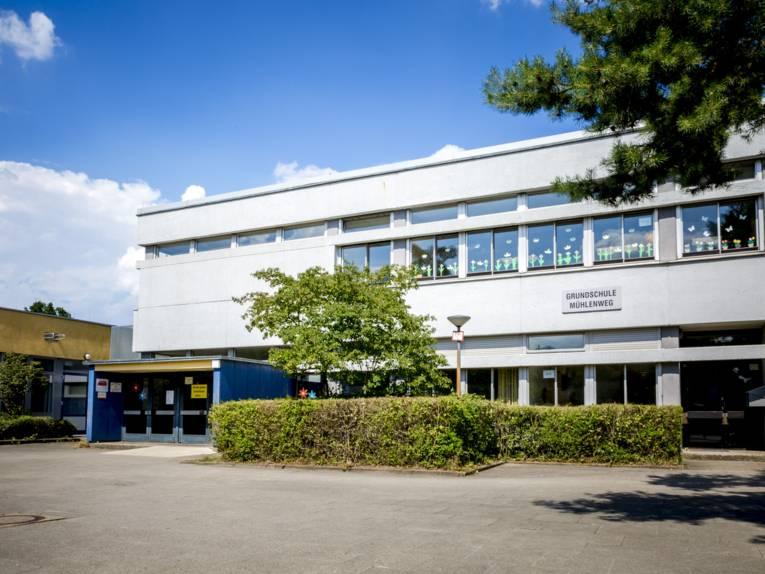 """Eingang zu einem zweigeschossigen Schulgebäude, an dessen Fenster im Obergeschoss selbstgemachte Papierblumen befestigt sind. Darunter befindet sich das Schild """"Grundschule Mühlenweg""""."""