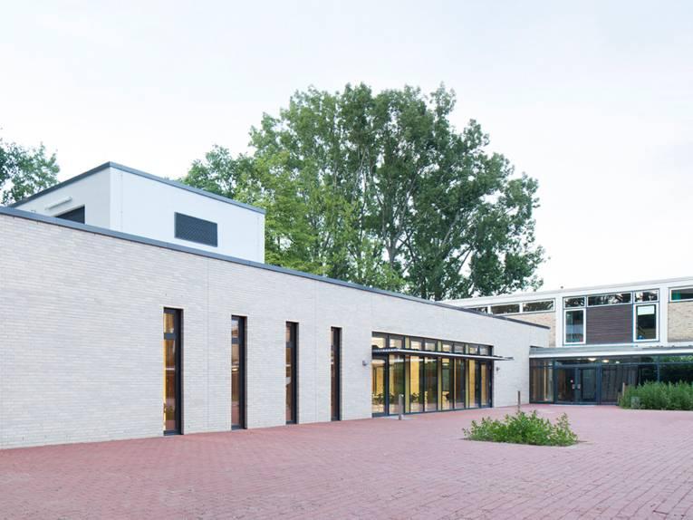 Außenaufnahme des eingeschossigen Mensa-Neubaus aus hellbeigem Klinker neben dem zweigeschössigen Bau der Wilhelm-Busch-Schule