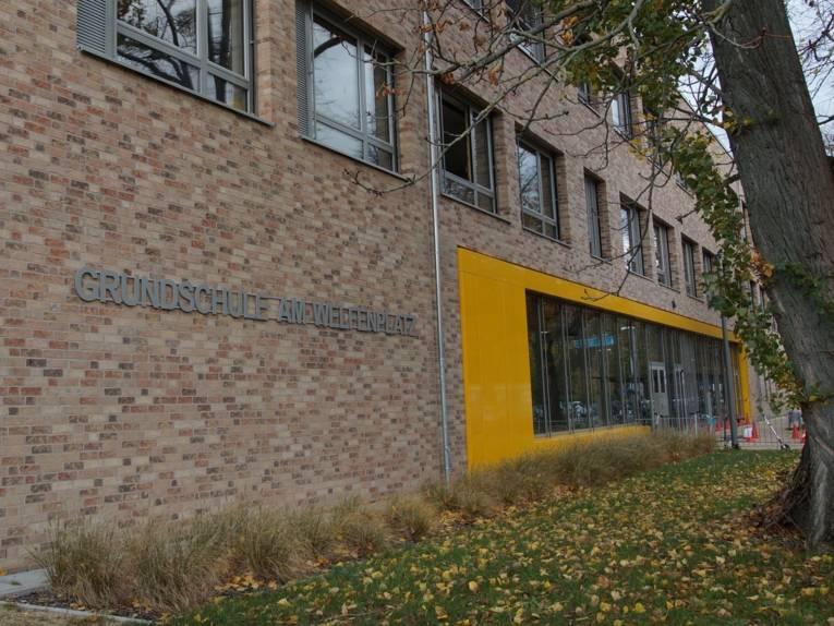 """Ein Schulgebäude von außen. Auf der Mauer steht """"Grundschule am Welfenplatz""""."""