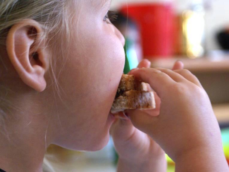 Kind beißt in ein Brot