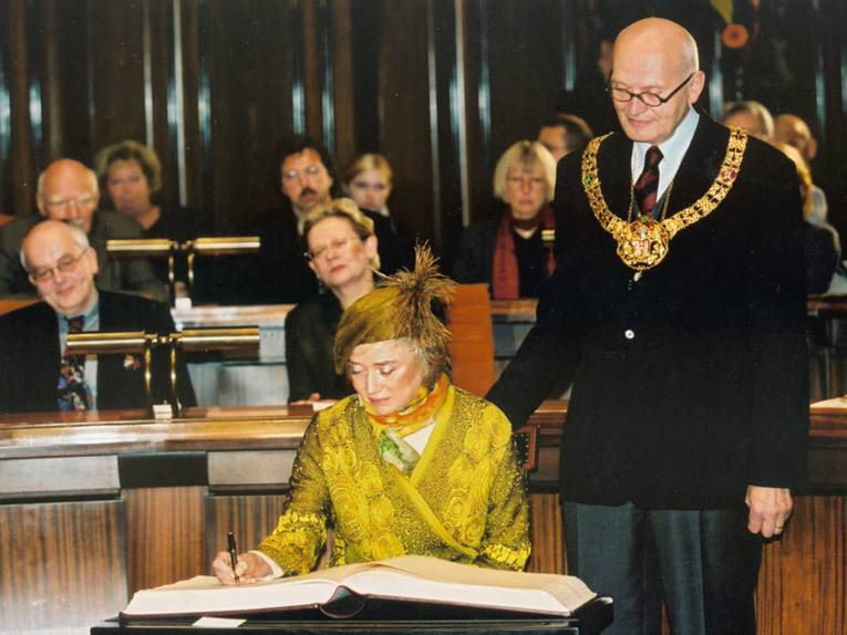 A lady in a yellowish dress signs a book, next to her a bald-headed man watching over her shoulder; many more people in the background