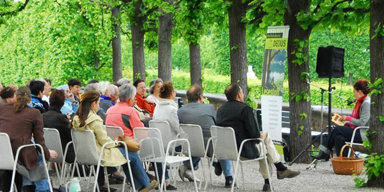 Eine Gruppe Menschen bei einer Lesung im Großen Garten