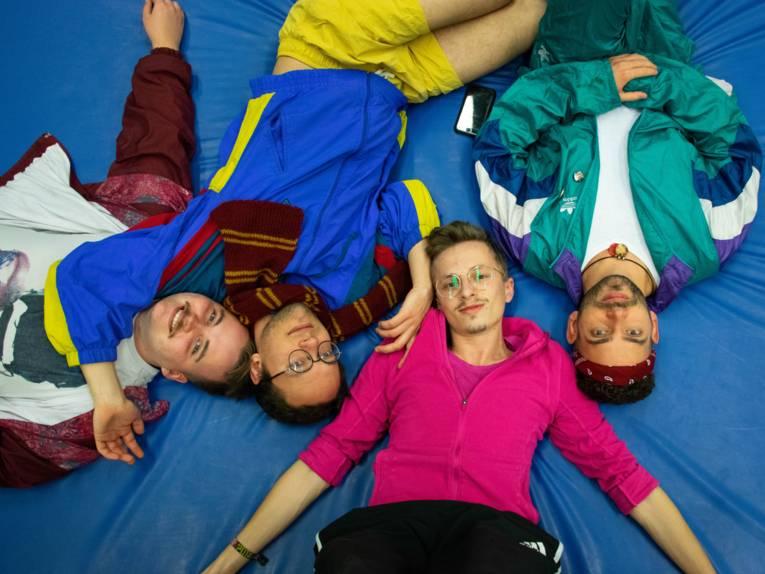 Vier Männer auf Sportmatten.