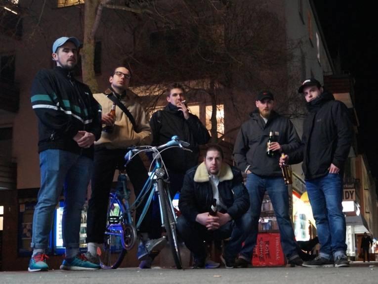 Sechs Männer mit Bierflaschen.