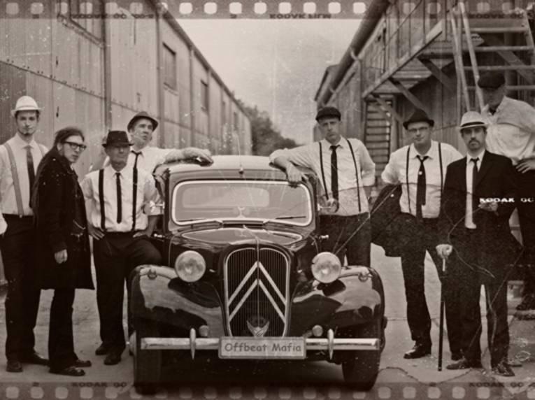 Acht Männer um ein Auto.
