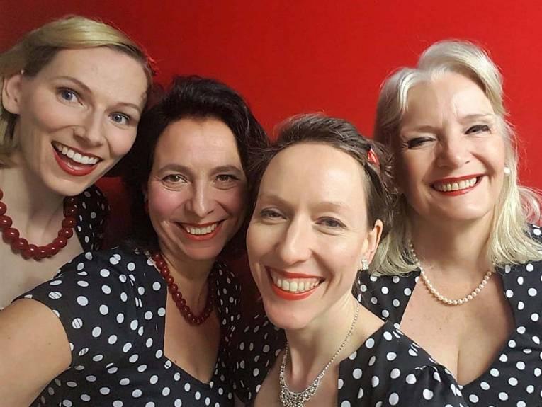 Vier lächelnde Frauen.