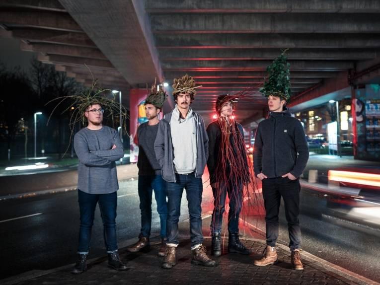 Fünf Männer unter einer Brücke.