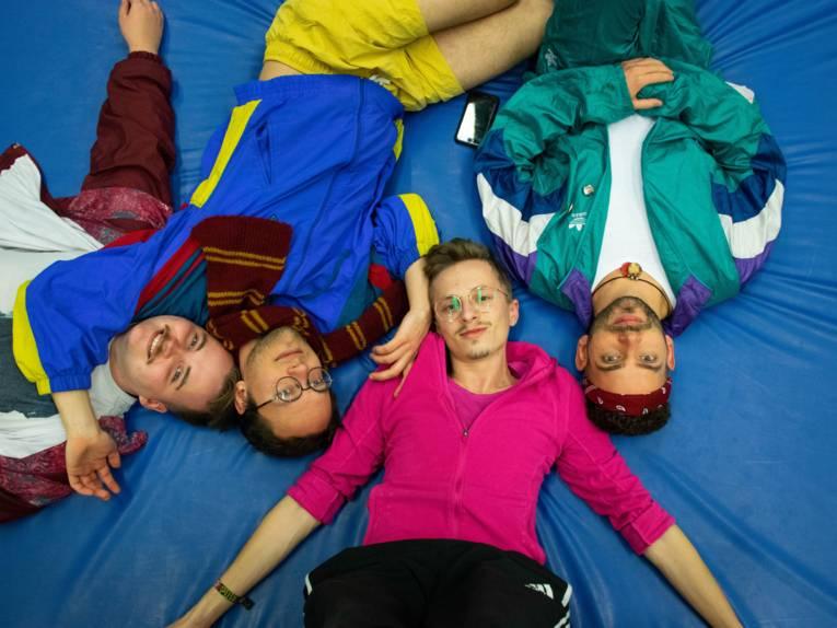 Vier junge Männer auf einer Sportmatte.
