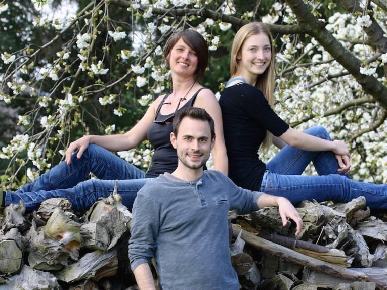 Zwei Frauen auf Holzstämmen, davor ein Mann.
