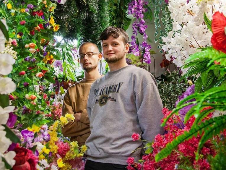 Zwei Männer inmitten eines Blumenmeeres.