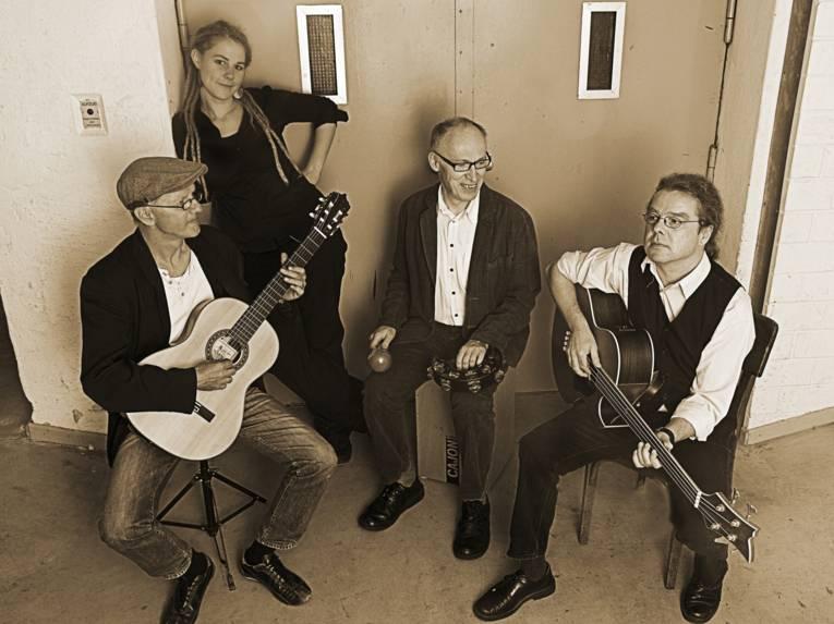 Drei Männer und eine Frau mit Instrumenten.