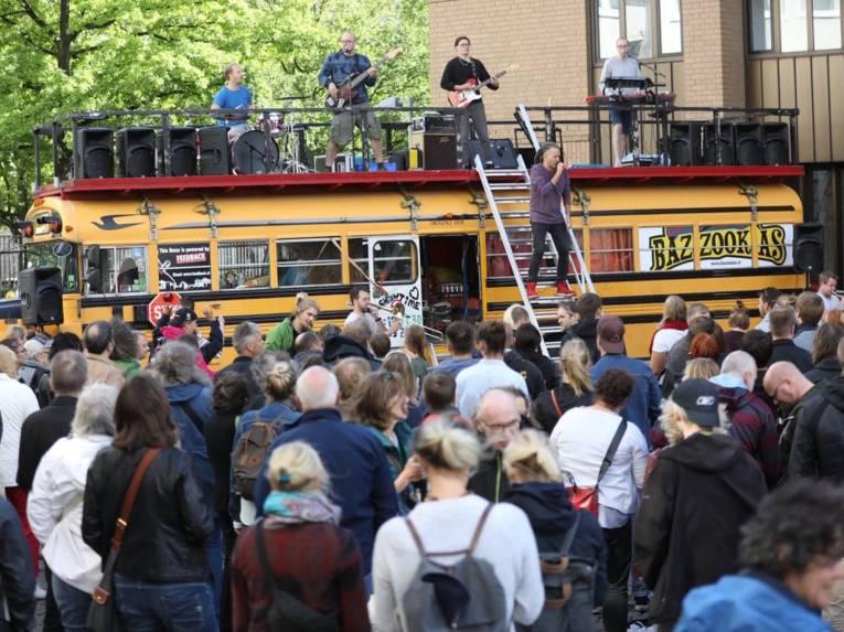 Menschen vor und auf einem Bus.