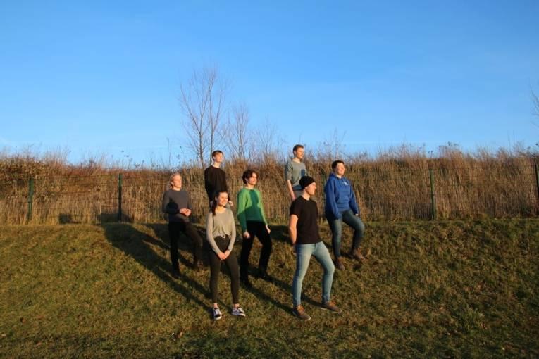 Sieben Männer und Frauen auf einer Grünfläche.