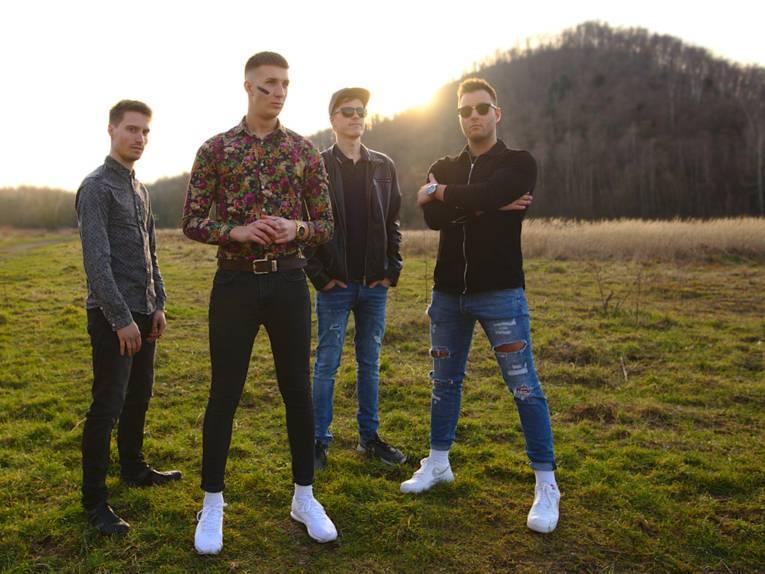 Vier junge Männer der Band RedNight stehen auf einer Wiese.