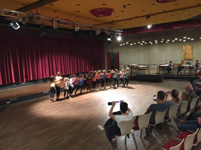 """Die Kinder aus dem Kinderzirkus """"Cirque d'Oehren"""" tanzen als """"Schlange"""" durch den Saal."""