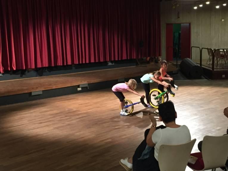 Drei Kinder verbeugen sich mit ihren Einrädern vor dem Publikum.