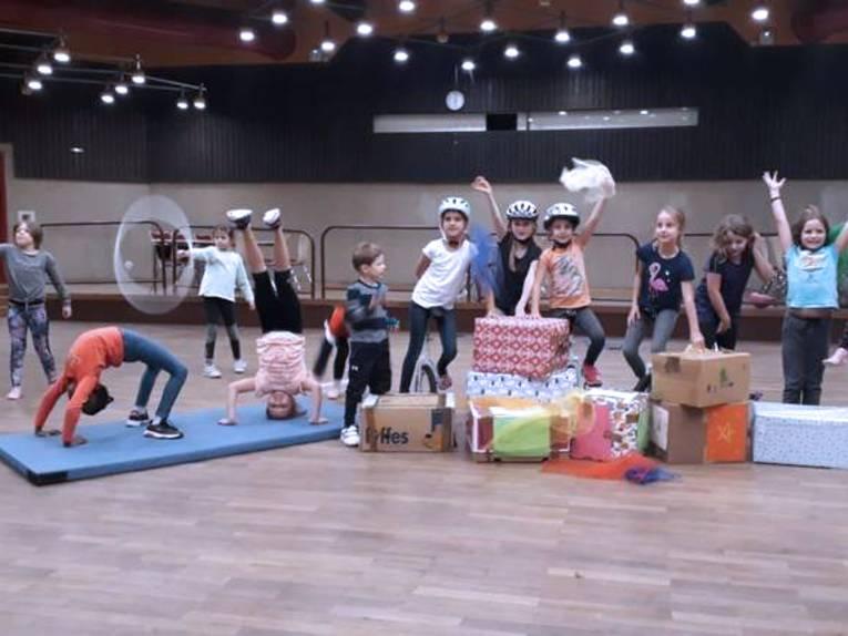 Mehrere Kinder machen verschiedene Zirkuskunststücke. Im Vordergrund liegen einige Weihnachtspäckchen.
