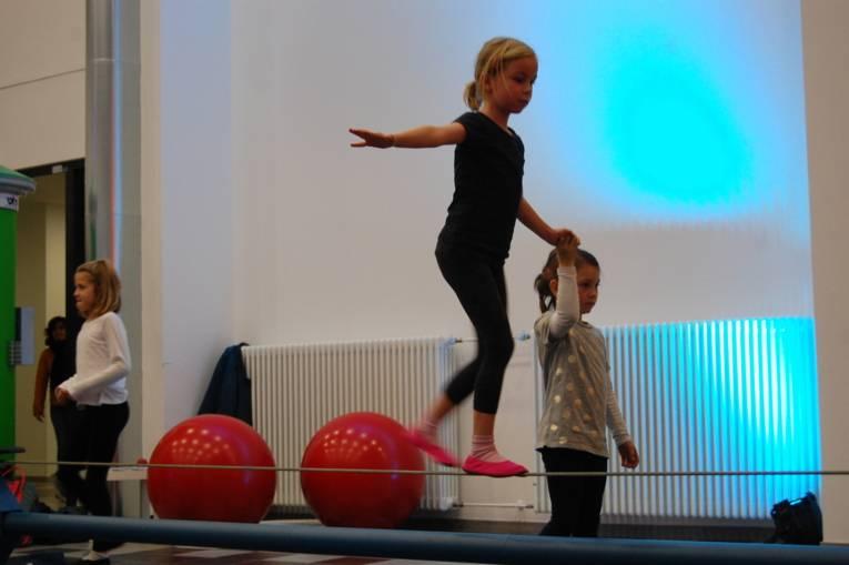 Ein Mädchen wird von einem anderen über ein gespanntes Seil geführt.