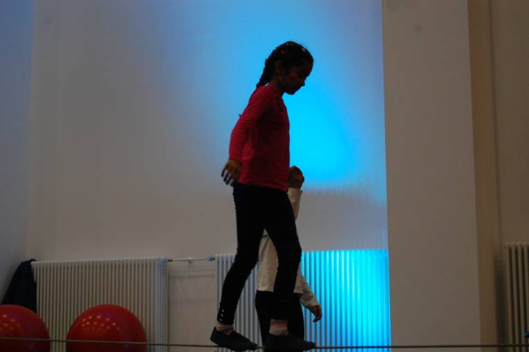 Ein Mädchen tanzt auf einem Seil.
