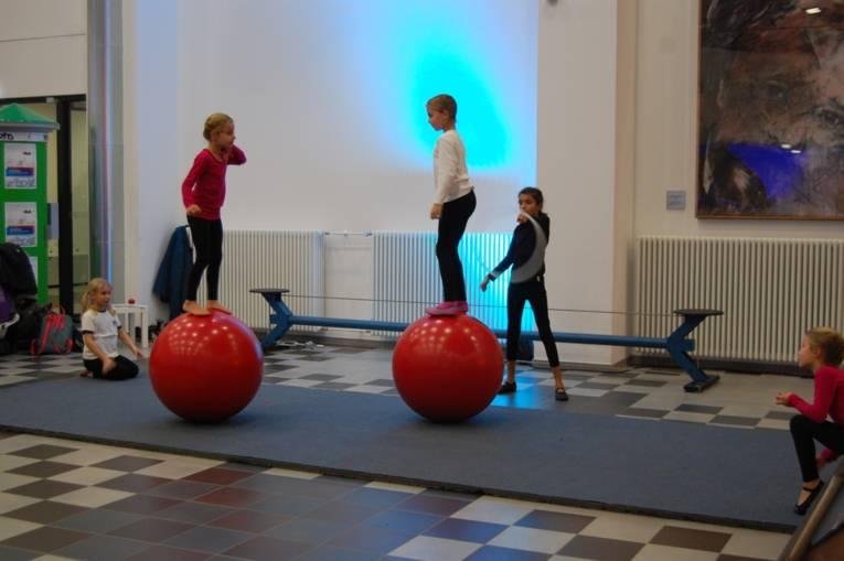 Zwei Mädchen balancieren auf großen, roten Kugeln.