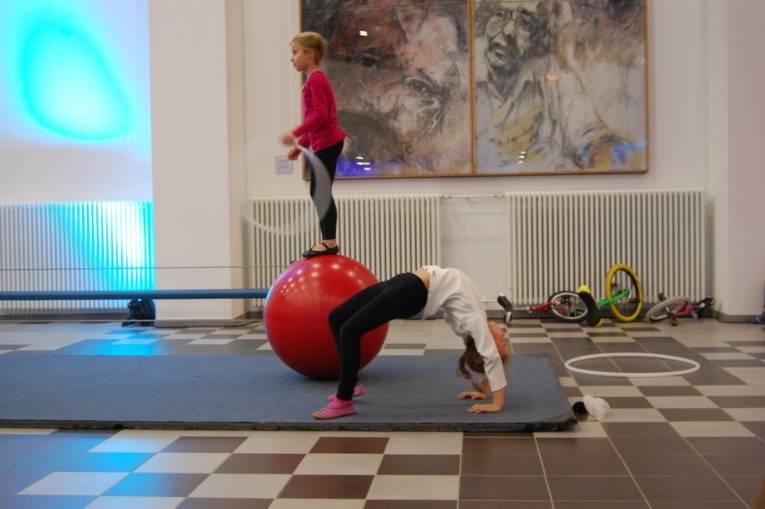 Ein Mädchen balanciert auf einer Kugel, davor macht ein anderes Mädchen eine akrobatische Figur.