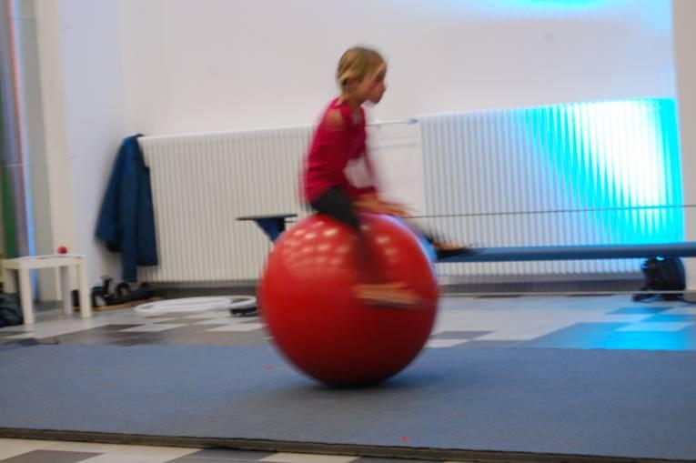 Ein Mädchen springt über eine große rote Kugel.