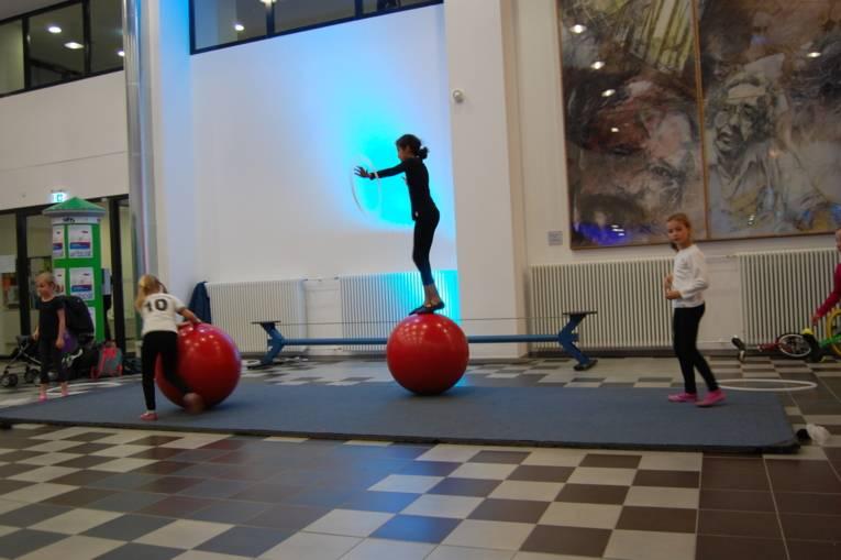 Ein Mädchen tanzt auf einer großen roten Kugel.