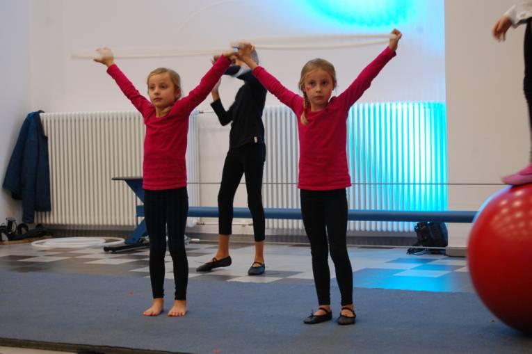 Zwei Mädchen verbeugen sich, nachdem sie eine akrobatische Figur gemacht haben.