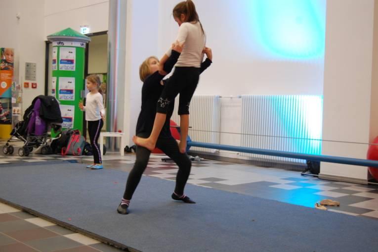 Ein Mädchen steht bei einem anderen auf den Knien. Sie machen Akrobatik.